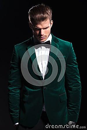 Man in a green velvet suit is looking down
