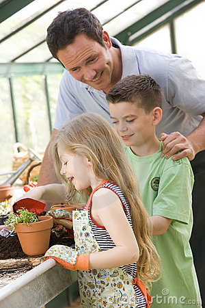 Man in greenhouse helping two young children