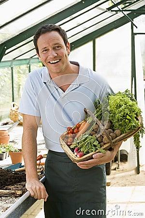 Man in greenhouse holding basket of vegetables