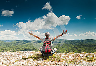 Man greeting nature on the top of mountain Stock Photo