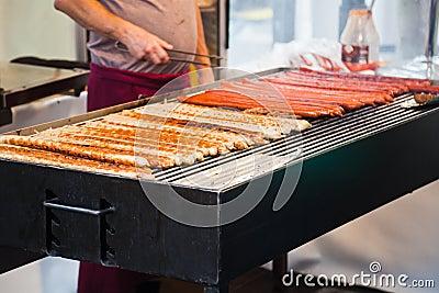 Man grills Frankfurter sausages