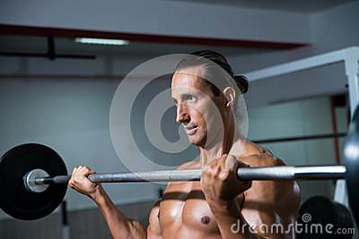 Man In The Gym Exercising Biceps With Barbell