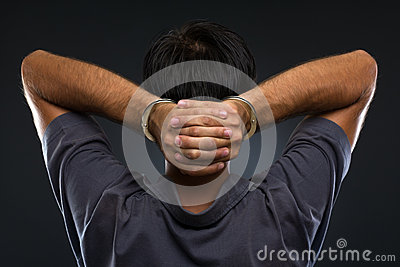 Man in handcuffs on gray background