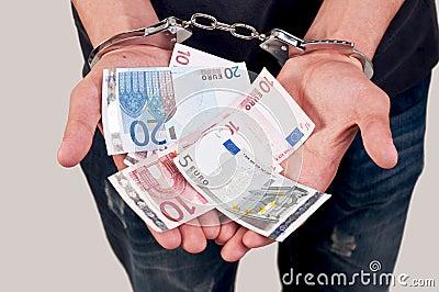 Man in handcuffs holding money