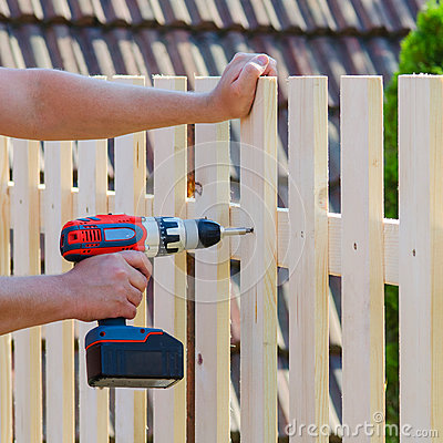 Free Man Hands Building Wooden Fence With A Drill And Screw. DIY Concept. Close Up Of His Hand And Tool. Stock Image - 99247141