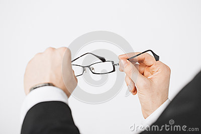 Man hands holding eyeglasses