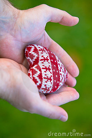 Man hands with red knitted heart
