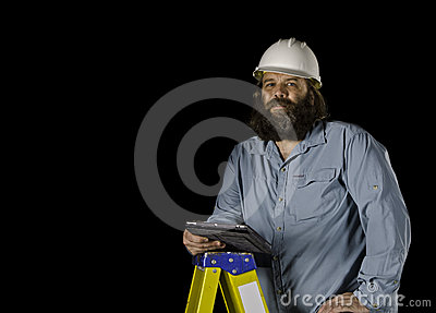 Man in hard hat holding a tablet on a step ladder