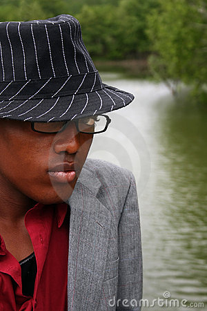 Man with hat in front of river