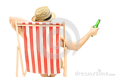 Man with hat sitting on a beach chair and holding a beer bottle