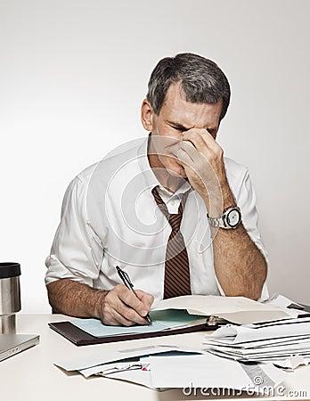 Man with Headache Paying Bills