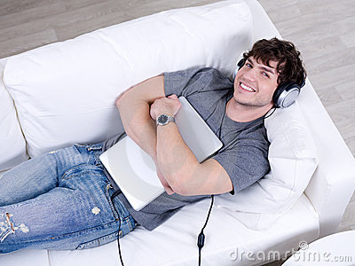 Man in headphone with laptop in an embrace