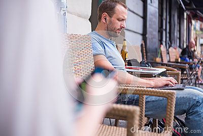 Man with headphones sitting outdoors using a laptop computer.