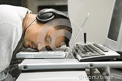 Man with headphones sleeping on laptop.