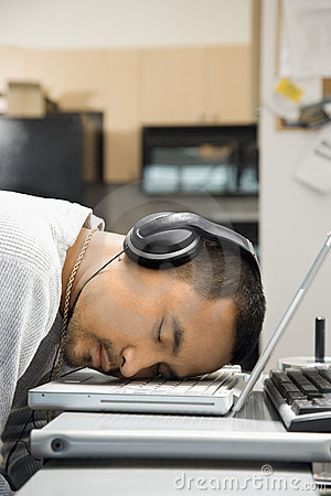 Man with headphones sleeping on laptop.