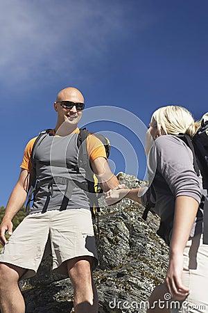 Man Helping Woman Climb Onto A Boulder