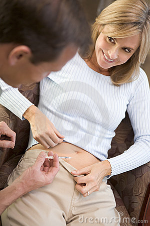 Man helping woman inject drugs to gain pregnancy