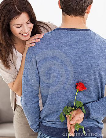Man hiding a flower behind his back for his wife