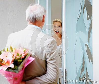 Man hiding a  flower bouquet for a surprised woman