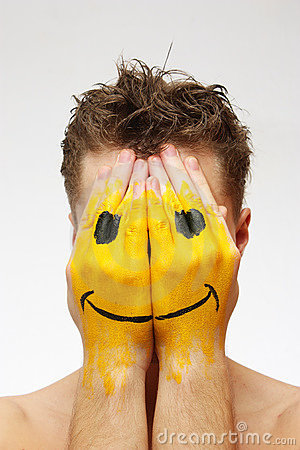 Man hiding his face under smile mask