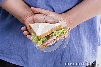 Man hiding sandwich