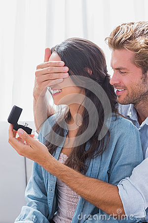 Man hiding wifes eyes to offer her an engagement ring