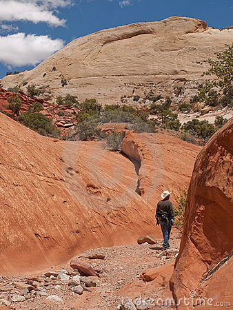Man hiking in narrow red sandstone canyon