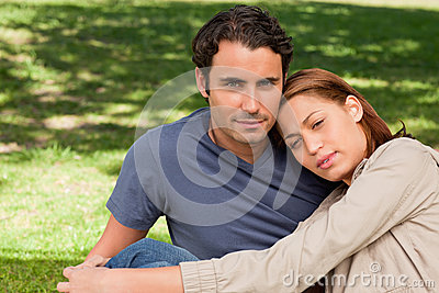 Man with his friend who is resting her head on his shoulder