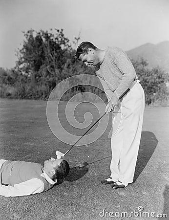 Free Man Hitting Golf Ball On Mans Forehead Stock Image - 52001841