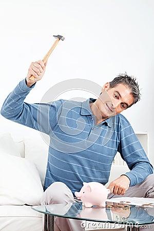 Man hitting piggy bank with hammer