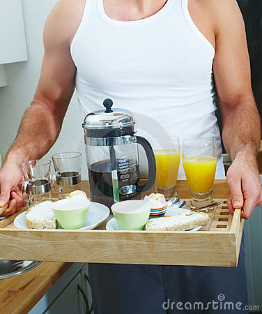Man holding a breakfast tray at home