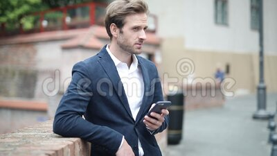 Man holding briefcase and leaning elbow on brick wall is reading news on his smart phone. Young businessman holding briefcase and leaning elbow on brick wall is stock video footage