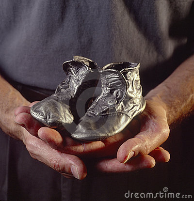 Man holding bronzed baby shoes
