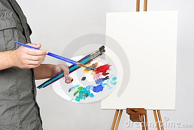 Man holding brushes and palette, canvas on easel