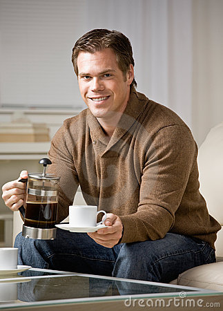 Man holding coffee carafe pouring cup of coffee