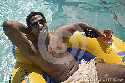 man-holding-drink-relaxing-inflatable-ra