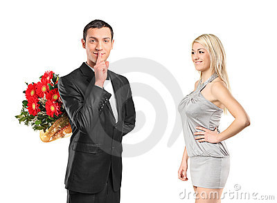 Man holding flowers, gesturing silence