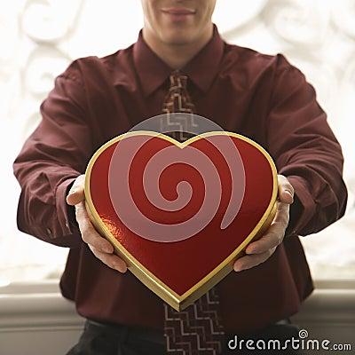 Man holding heart shaped box.