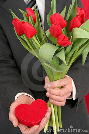 Man Holding Heart Shaped Box and Flowers