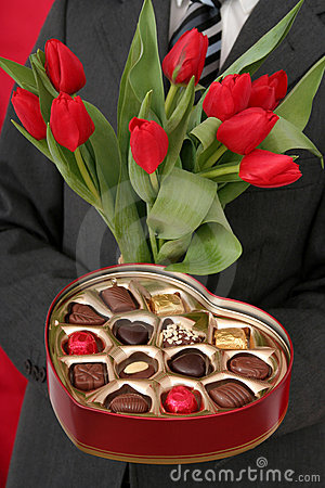Man Holding Heart Shaped Box and Tulips