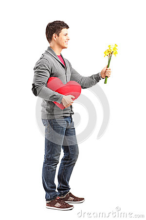 Man holding a heart shaped object and flowers