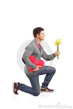 Man holding a heart shaped pillow and flowers