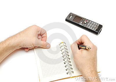 Man holding pen and writing in weekly planner,