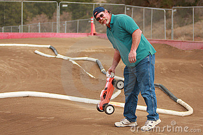 Man holding RC car at race track