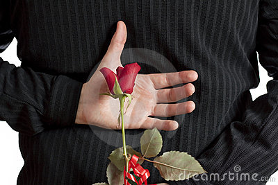 Man holding red rose behind his back