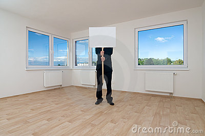 Man holding sign in empty room