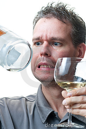 Man holding wine glass and empty bottle
