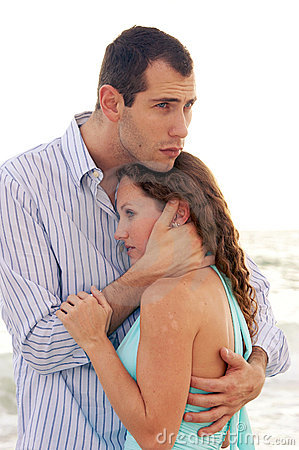 Man holding woman close comforting her