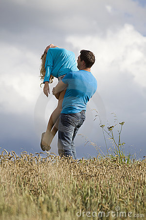 Man holding woman up in air