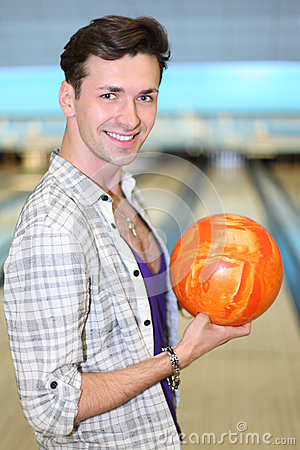 Man holds ball in bowling club
